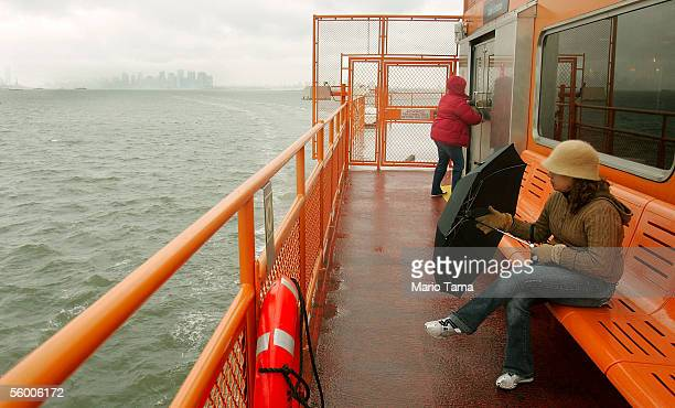 A woman closes her umbrella while riding the Staten Island ferry on its 100th anniversary October 25 2005 in New York City In 1905 the ferries were...