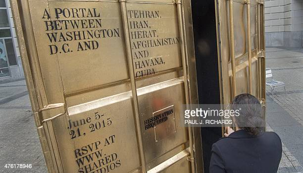 Woman closes the door on the Golden Shipping Container after making a free video call in the courtyard of the Woodrow Wilson Building in Washington,...
