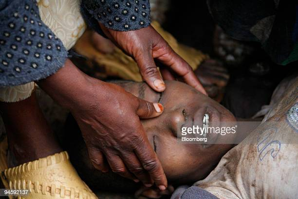 IMAGE CONTAINS GRAPHIC CONTENT A woman closes the eyes of a 16yearold girl known only as Regina who was shot dead by police in the Kibera area of...