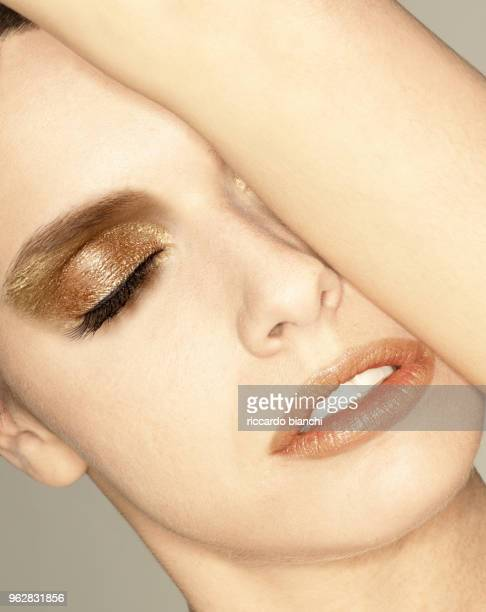 woman close-up with gold eyeshadow and closed eyes and parted lips
