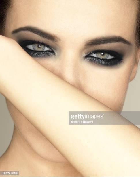 woman close-up with green eyes and black eyeshadow - sombra maquiagem de olho - fotografias e filmes do acervo