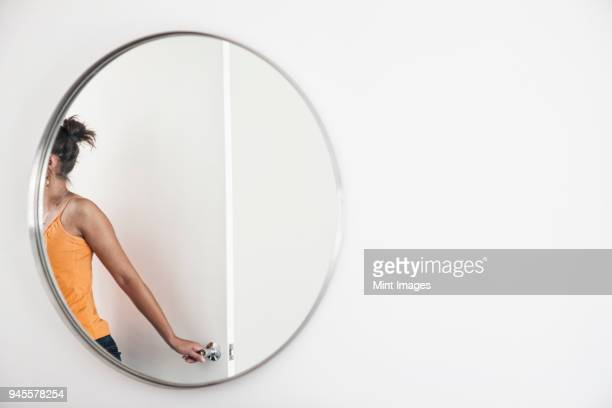 Woman closing a door in a room, reflected in a round mirror.