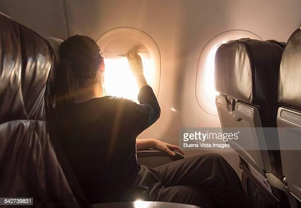 Woman closing airplane window at sunset