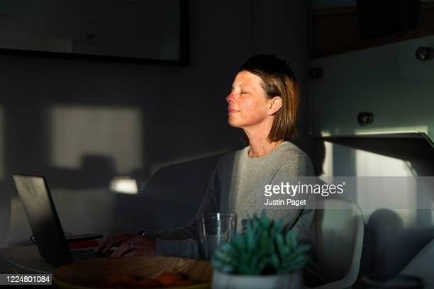 woman closing her eyes as the last sun rays of the day come into her house - wellness stock pictures, royalty-free photos & images