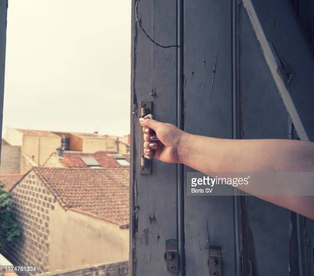 woman closing shutters in a country house - 建具 シャッター ストックフォトと画像