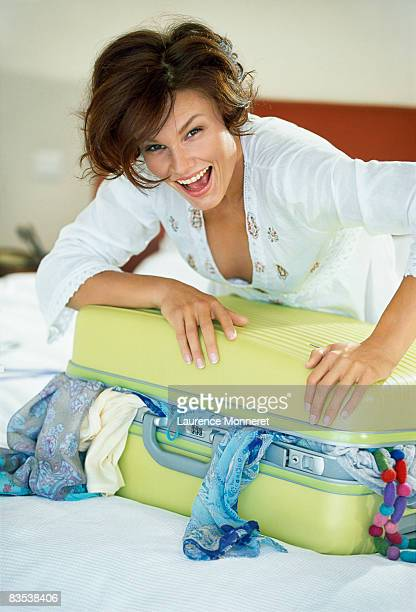 Woman closing suitcase overflowing clothes