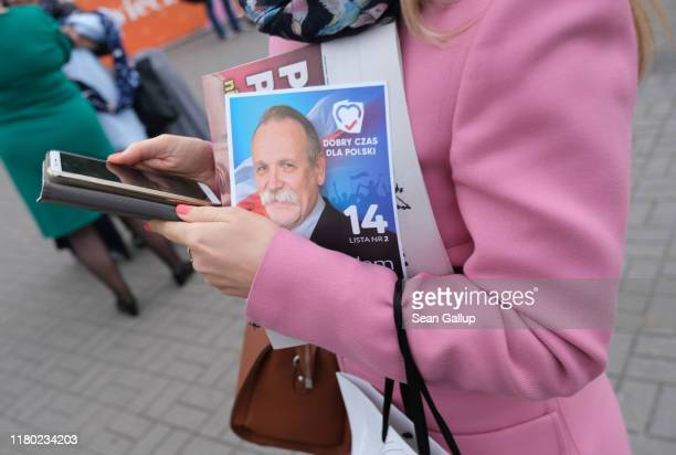 A woman clutches an election flyer from the Law and Justice political party during rush hour on October 10 2019 in Warsaw Poland Poland is due to...