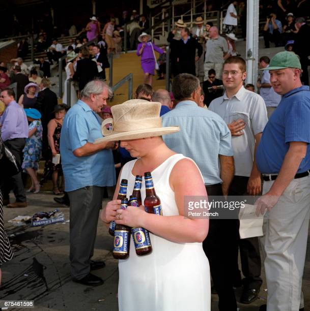 A woman clutches five bottles of lager on Ladies Day at Royal Ascot June 2001