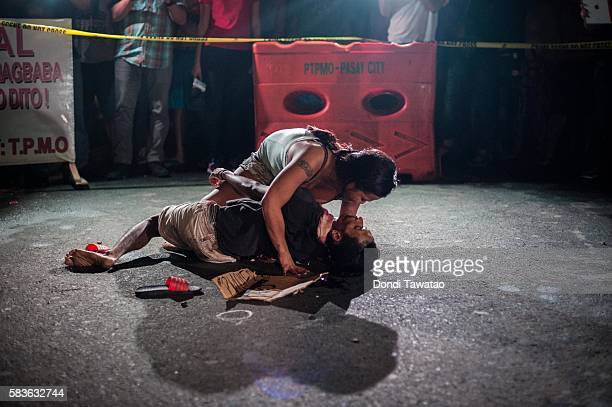 A woman clutches her dead husband in grief after armed assailants in a motorcycle shot him in a main thoroughfare on July 23 2016 in Manila...