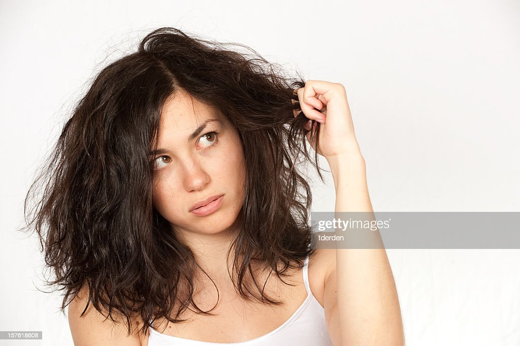 Woman clutching wavy dark hair over a white background : Stock Photo
