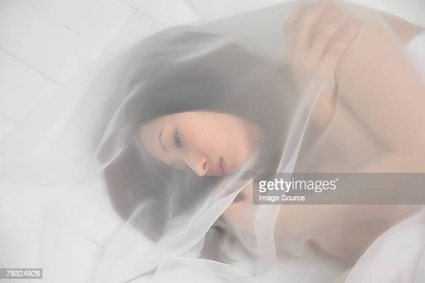 Woman cocooned in a sheet