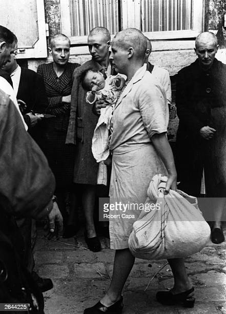 Woman collaborator and her baby, whose father is German, returns to her home after having her head shaven following the capture of Chartres by the...