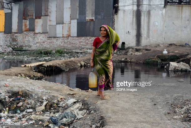 Woman collecting drinking water in an industrial area. Dhaka is going back to its normal life after some months of the ongoing pandemic.