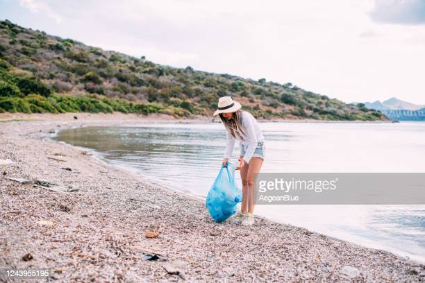 woman collecting garbage on the beach - altruism stock pictures, royalty-free photos & images