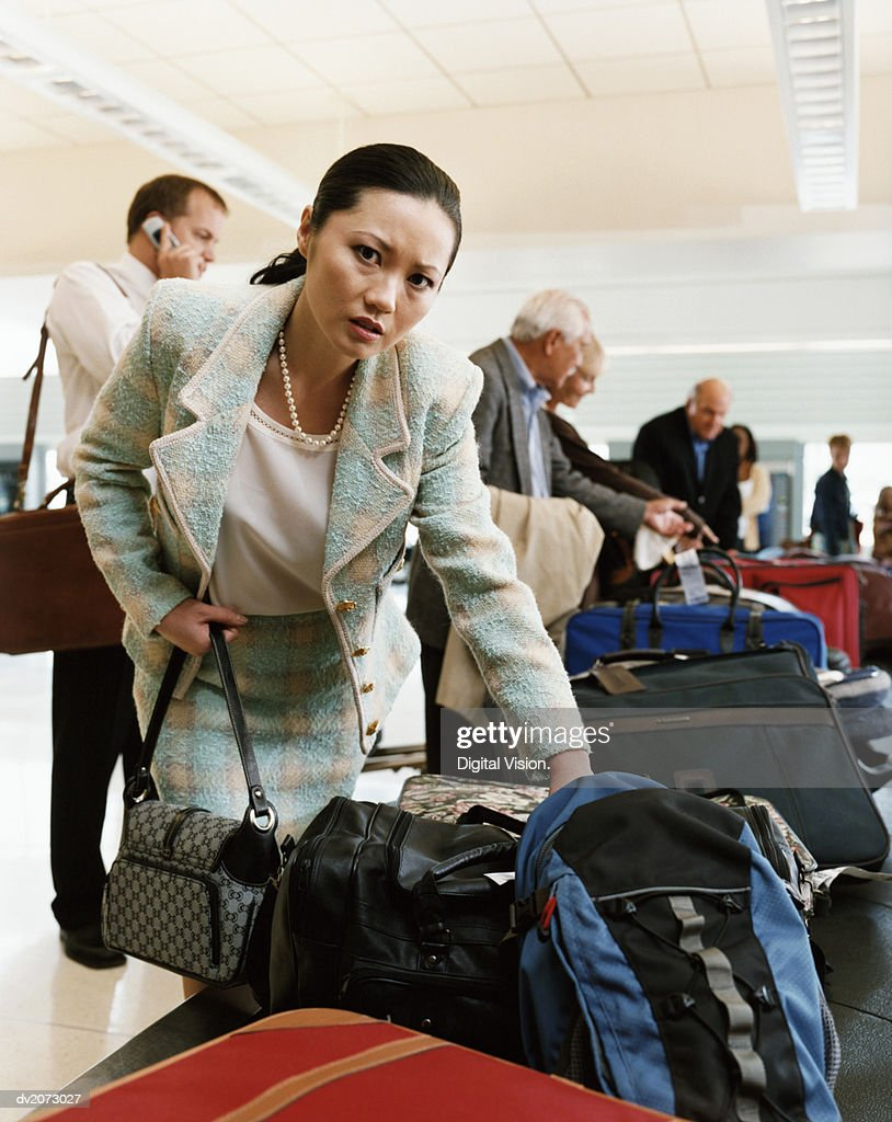 Woman Collecting Luggage at an Airport Baggage Collection : Stock Photo