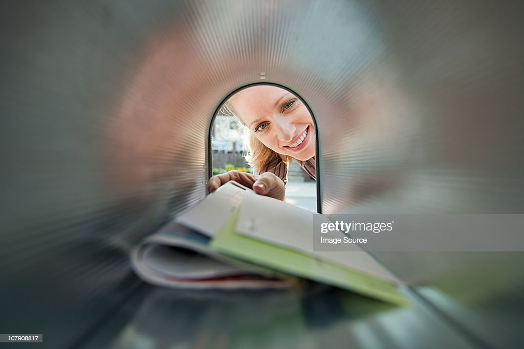 Woman collecting mail from mailbox : Stock Photo