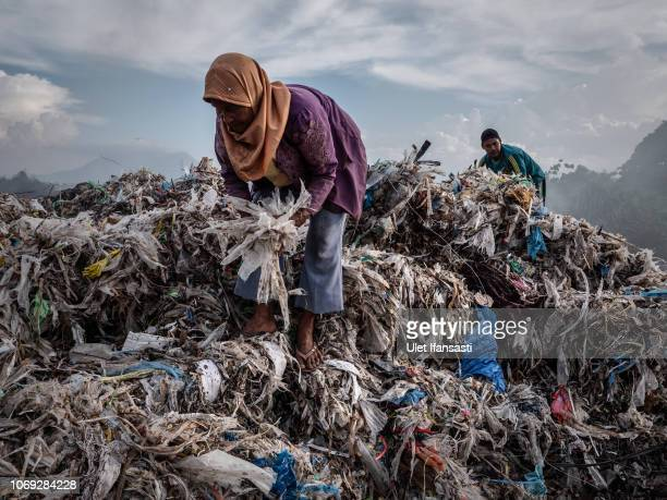 Woman collecting plastic to recycle at a import plastic waste dump in Mojokerto on December 4, 2018 in Mojokerto, East Java, Indonesia. Indonesia's...