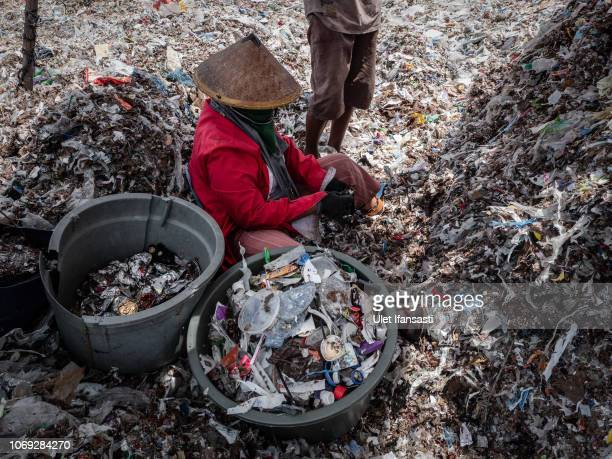 Woman collecting plastic to recycle at a import plastic waste dump in Mojokerto on December 5, 2018 in Mojokerto, East Java, Indonesia. Indonesia's...