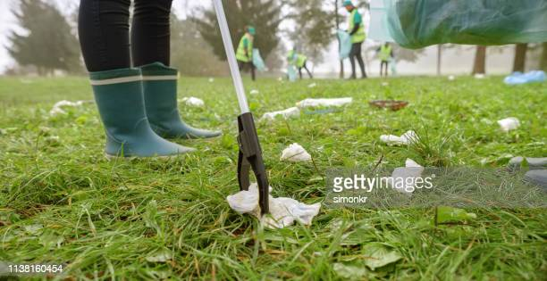 woman collecting rubbish with waste picker - picking stock pictures, royalty-free photos & images