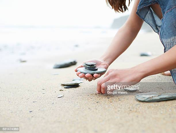 Woman collecting small rocks on beach