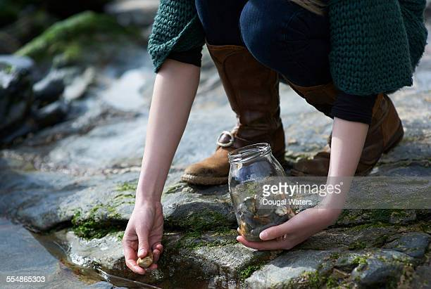 Woman collecting stones in jam jar, close up.