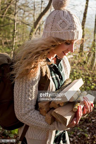 Woman collecting wood for fire by seaside