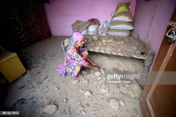 A woman collects debris due to shelling inside her damaged home at Jabowal village in Arnia sector near the IndiaPakistan international border on...