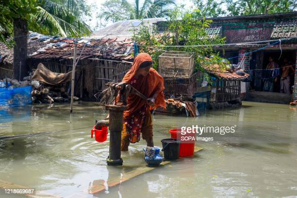 Woman collects drinking water from a tube well in a flooded area. Thousands of shrimp enclosures have been washed away, while numerous thatched...