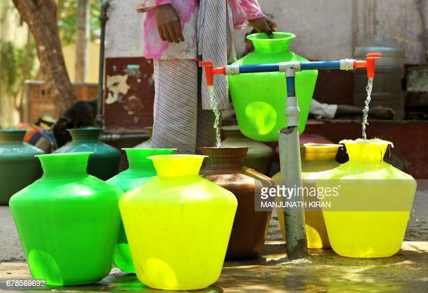 A woman collects drinking water in plastic pots from a community tap in Bangalore on March 20 2012 in wake of the annual 'World Water Day' observed...