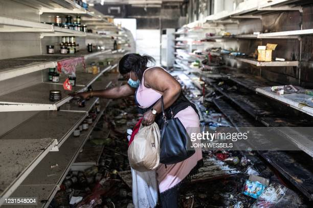 Woman collects food and drinks from a burnt down and looted Auchan supermarket in the up-market area of Almadies in Dakar on March 6, 2021 as...