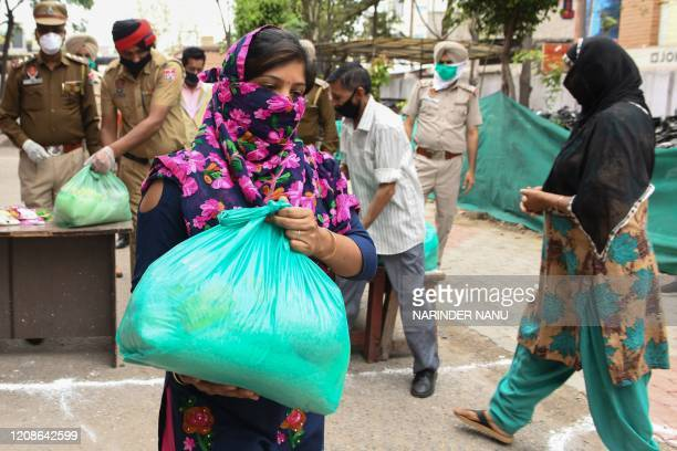 A woman collects free grocery iems distributed by police officials during a governmentimposed nationwide lockdown as a preventive measure against the...