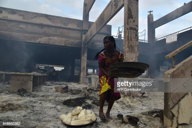 A woman collects items amid debris in the market after a fire devastated the building during the night on September 18 2017 in Abobo neighborhood of...