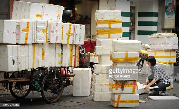 A woman collects polystyrene boxes for recycling on a street in Shanghai on September 26 2012 Japanese Prime Minister Yoshihiko Noda warned China in...