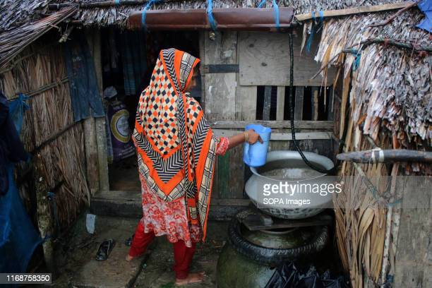 SHYAMNAGAR SATKHIRA KHULNA BANGLADESH A woman collects rainwater by using a plastic sheet under tin roof rainwater is the main source of drinking...