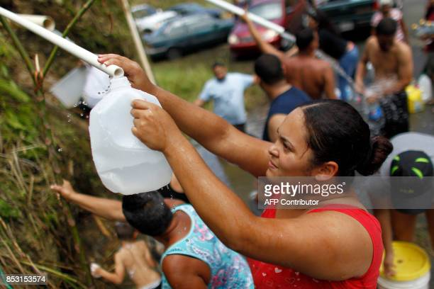A woman collects water from a natural spring created by the landslides in a mountain next to a road in Corozal west of San Juan Puerto Rico on...