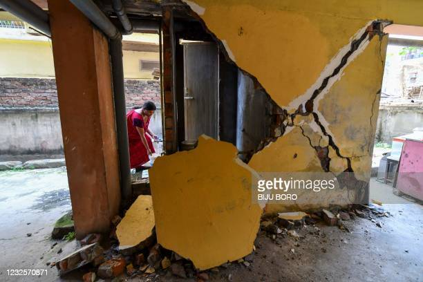Woman collects water from a tap near a collapsed wall at an apartment building in Guwahati on April 28 after a strong earthquake hit Assam in...