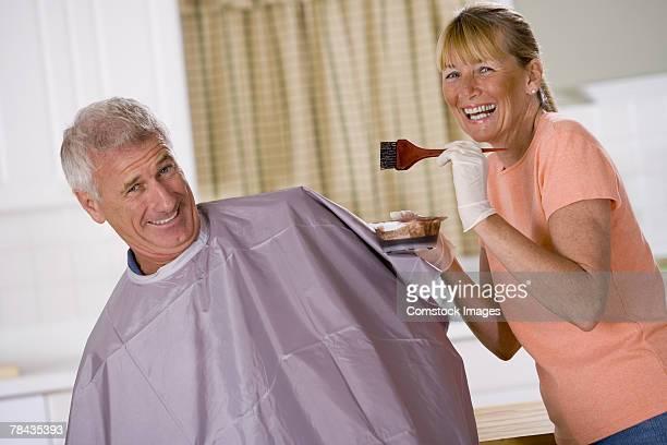 Woman coloring a man's hair