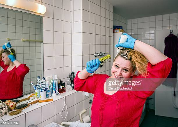 Woman coloring her own hair at home