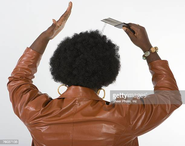 woman combing afro, against white background, rear view - african american 70s fashion stock photos and pictures