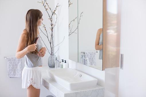 Woman combing hair in a bathroom - gettyimageskorea