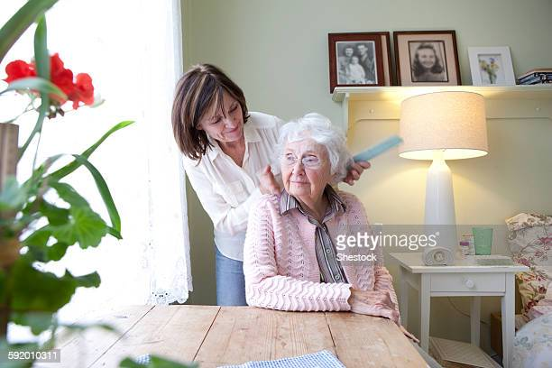 Woman combing hair of elderly mother