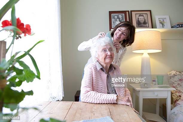 Woman combing hair of elderly mother