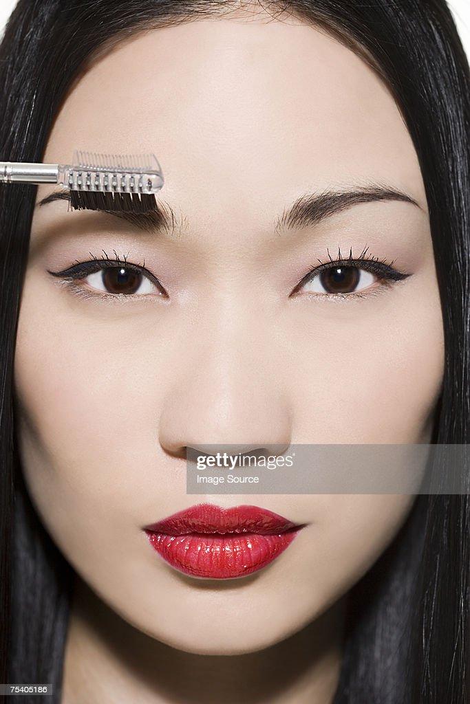 Woman combing her eyebrow : Stock Photo