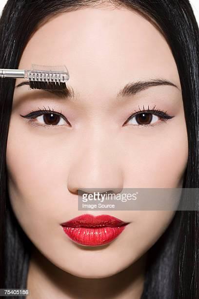 Woman combing her eyebrow