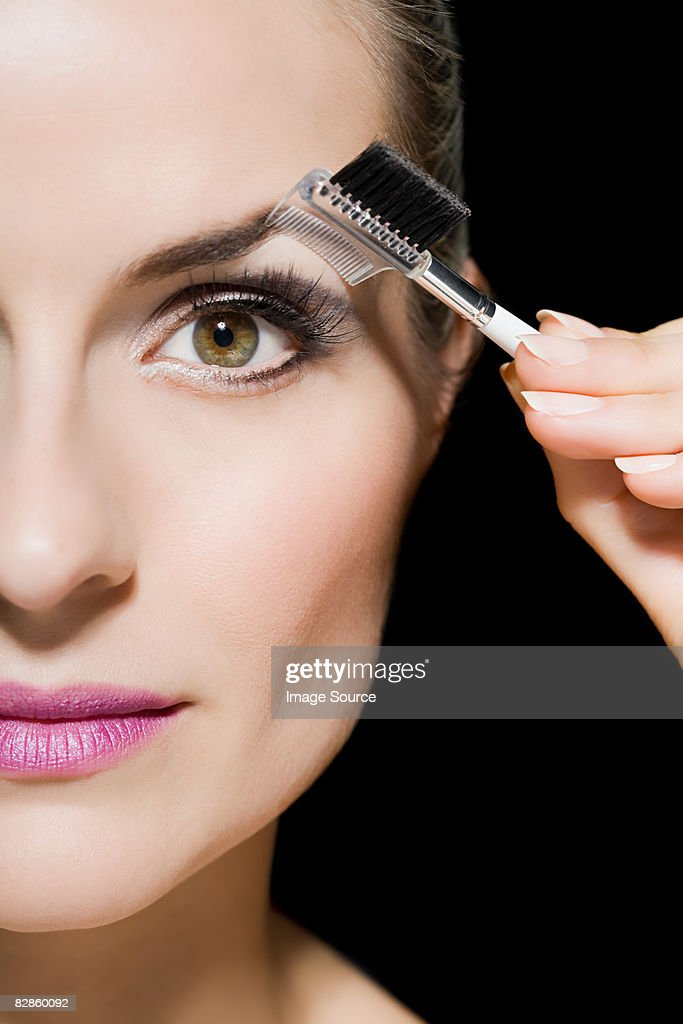 Woman combing her eyebrow : Stock Photo