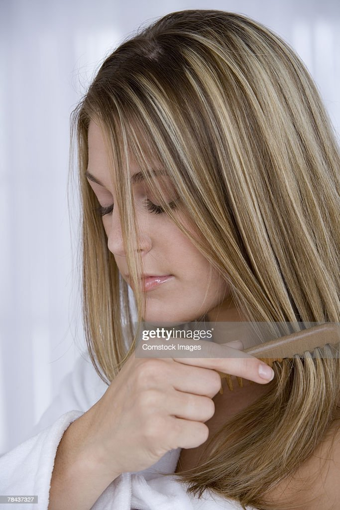 Woman combing her hair : Stockfoto