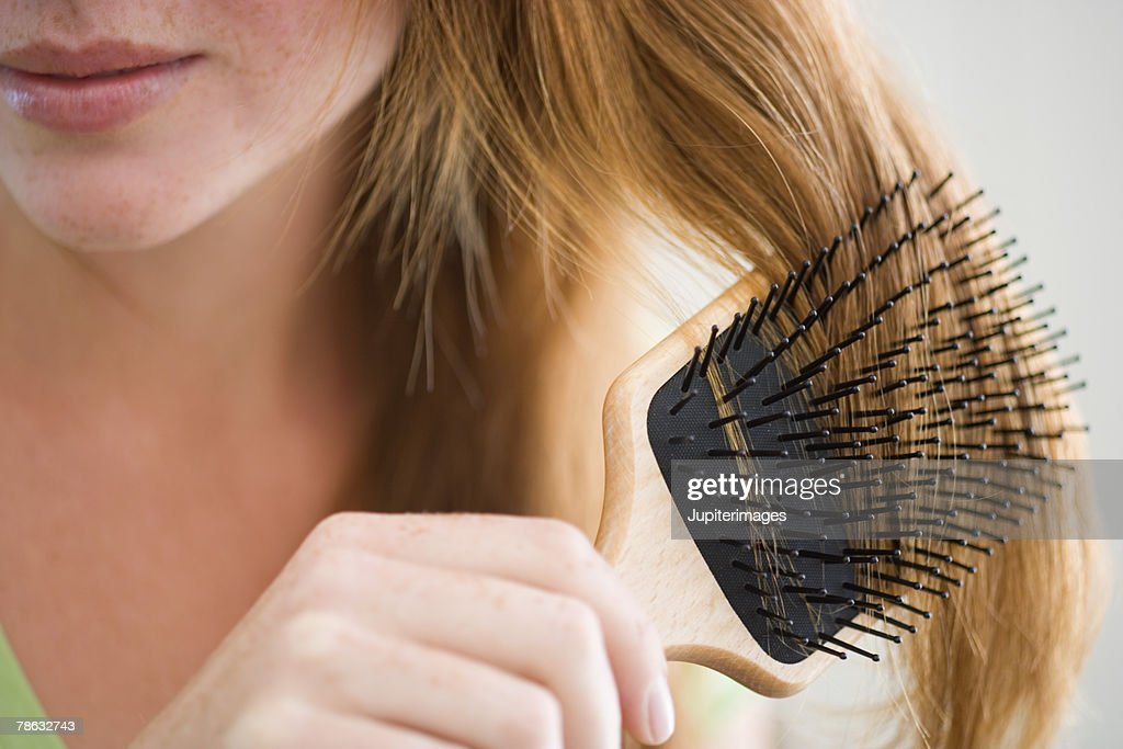 Woman combing her hair : Stock Photo