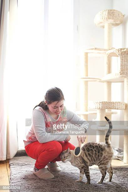 Woman combing her pet cat's hair