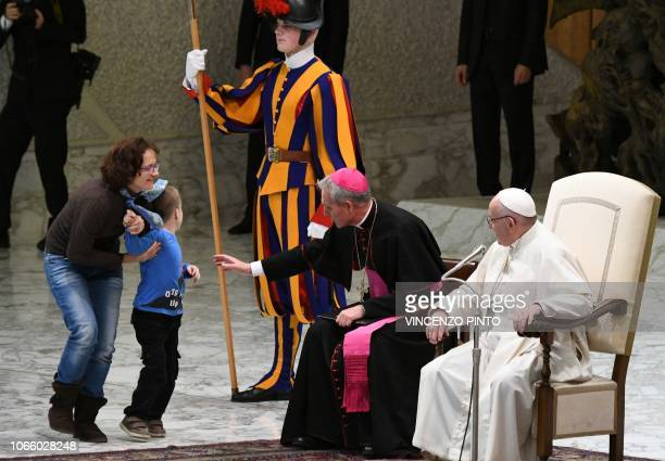 A woman comes get a boy who jumped on stage from the audience as Pope Francis and Prefect of the Papal Household Georg Ganswein look on during the...