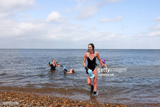 woman comes out of the water after open water swimming - menopossibilities stock pictures, royalty-free photos & images